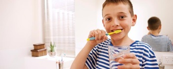A young boy brushing his teeth.